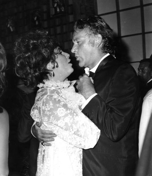 Elizabeth Taylor et son mari Richard Burton (1925 - 1984) danser ensemble lors de la soirée et bal donné par la comtesse Marina au Palais Vendramin à Venise.
